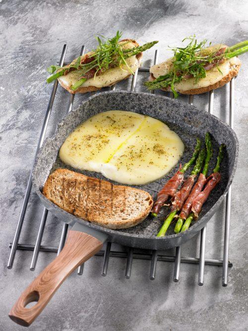 Una receta de una tostada de pan cn queso, jamón y espárragos