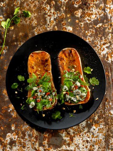 calabazas al horno servidas con queso y hierbas
